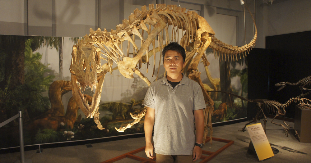 Yoshitsugu Kobayashi standing in front of the skeleton of an afrovenator dinosaur.