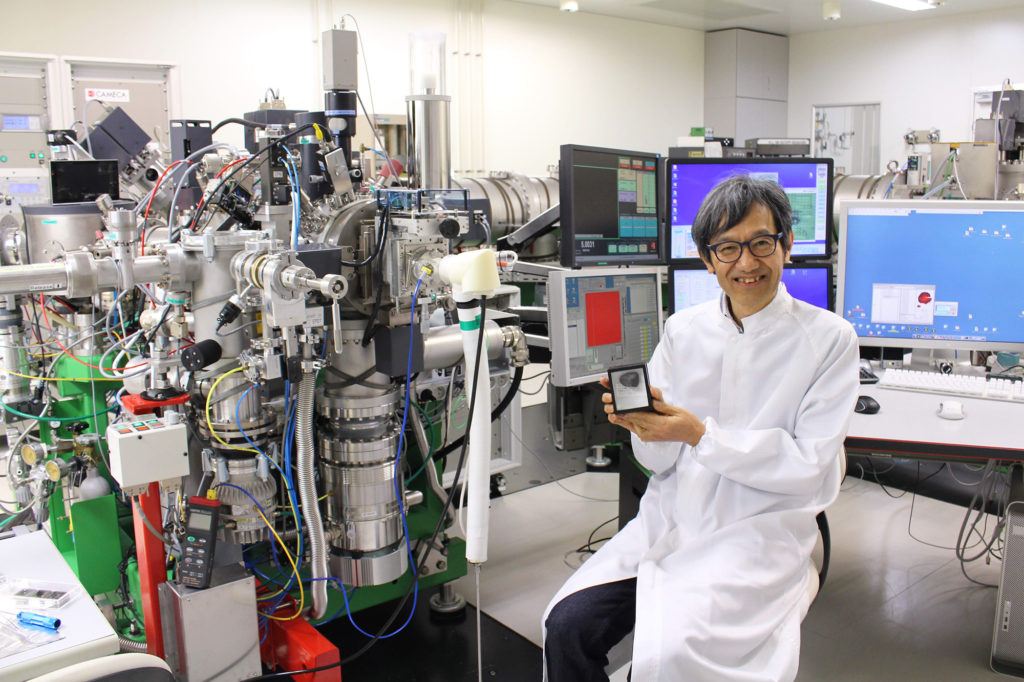 Dr. Yurimoto holding a meteorite in front of the isotope microscope.