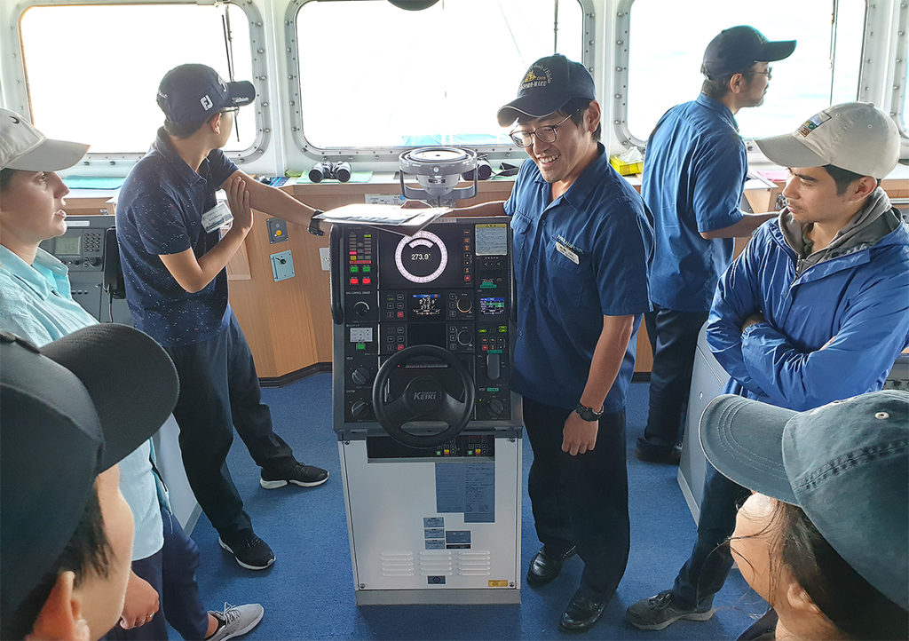 A crew member showing how to steer the ship.