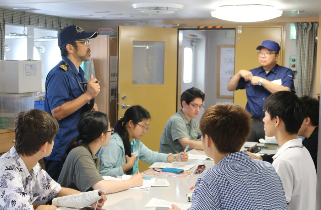 Crew members giving safety instructions and explaining the rules on the ship.