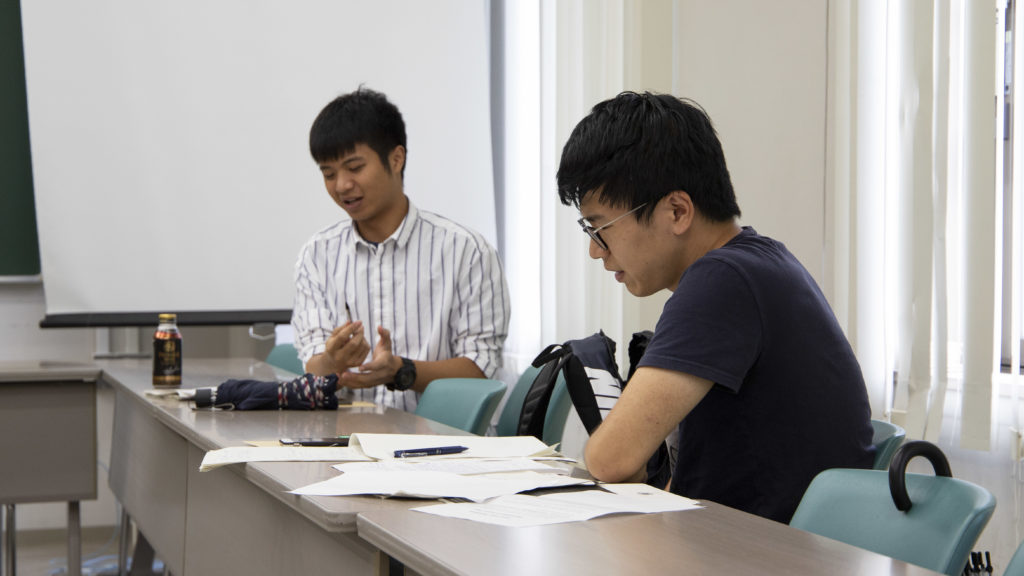 Master's student Chen Shi discussing policy making with one of his classmates.